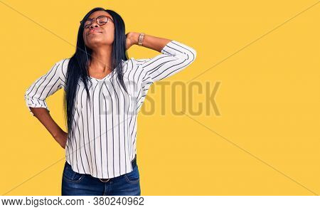 Young african american woman wearing casual clothes and glasses suffering of neck ache injury, touching neck with hand, muscular pain