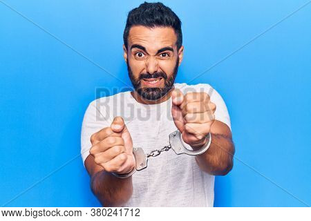 Young hispanic man wearing prisoner handcuffs annoyed and frustrated shouting with anger, yelling crazy with anger and hand raised
