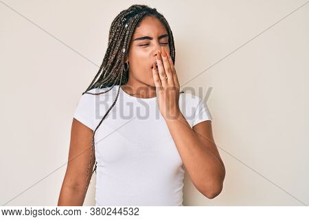Young african american woman with braids wearing casual white tshirt bored yawning tired covering mouth with hand. restless and sleepiness.