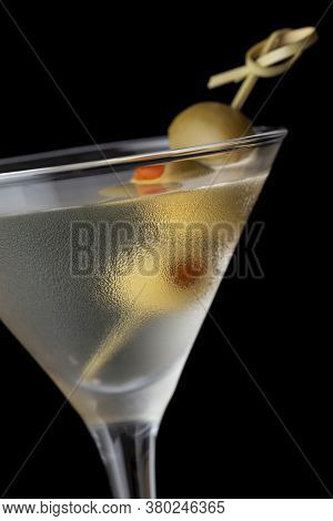 Macro Detail Of Martini Cocktail With Vodka, Dry Gin, Vermouth And Some Olives On A Decorative Woode