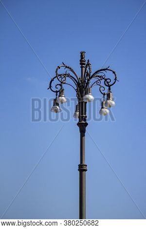 Ornate Wrought Iron Lamppost Situated In Front Of A Clear Blue Sky
