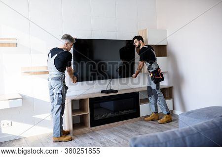 Full Length Shot Of Two Professional Technicians, Workers In Uniform Installing Television On The Wa