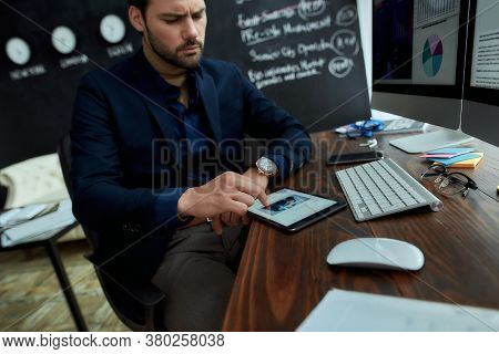 Young Focused Businessman Sitting At His Workplace In The Office And Using Digital Tablet, Reading F