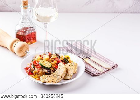 Roasted Chicken Breast With Grilled Zucchini, Eggplant And Red And Yellow Bell Peppers On White Plat