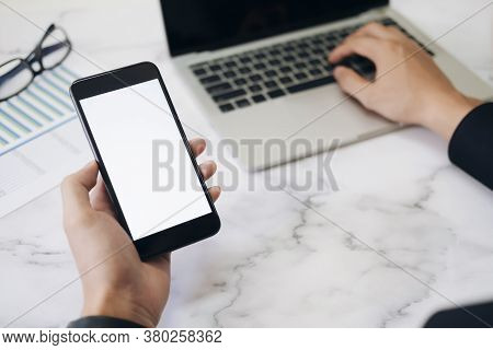 Closeup Hands Using Smartphone Mockup At The Office Desk. Blank Screen Mobile Phone For Graphic Disp