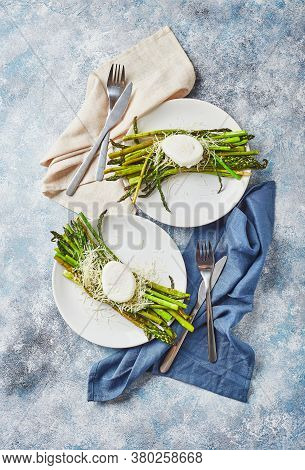 Green Asparagus With Poached Egg And Parmesan, Vegetarian Breakfast Served On White Plate On Light B