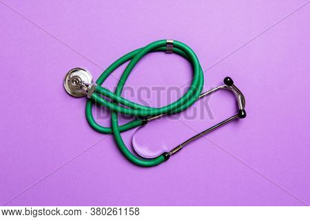 Top View Of Green Stethoscope On Colorful Background. Medical Diagnosis Tool Concept
