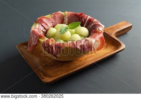 Melon With Air Dried Ham, Served In Halved Melon Stuffed With Serrano Ham And Melon Balls. On Rustic