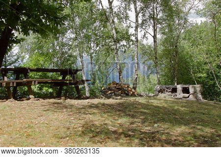 A Pic Nic Area In The Italian Alps With Wood Table And Raw Stone Barbeque. High Quality Photo