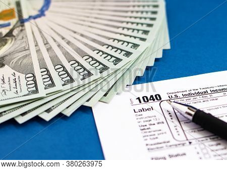 Tax Form 1040, Pen And Dollars On A Blue Table. The Concept Of Business Taxation And Business