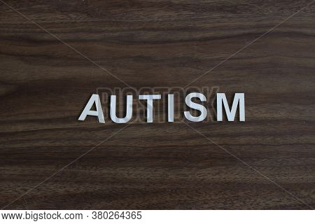 The Word Autism Spelled Out On A Wooden Background