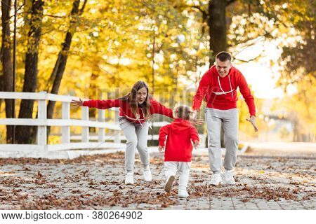 Father, Mother And Little Daughter Are Walking In The Autumn Park, Happy Family Is Having Fun Outdoo