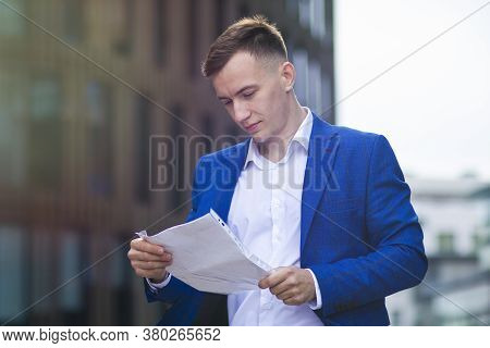 Serious European Concentrated Businessman Focusing On Reading Documents. Handsome Young Guy In Forma