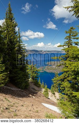 Blue Water In A Forest Lake With Pine Trees, View Of A Beautiful Lake With Blue Sky From Some Pine T