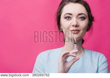 Woman Cosmetologist Doctor With A Syringe In Hands On A Pink Background In The Studio. The Concept O