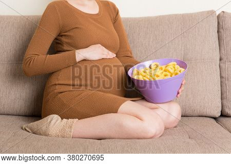 Close Up Of Pregnant Woman Sitting On The Sofa Is Eating Chips Because Of Salt Cravings. Unhealthy J