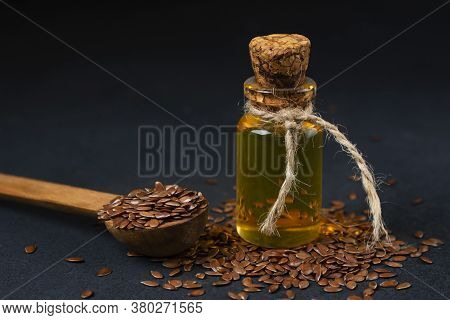Linseed Oil Bottle And Flax Seeds On A Dark Background.