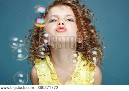 Child With Soap Bubbles. Little Girl Blowing Soap Bubbles In The Studio. High Quality Photo.