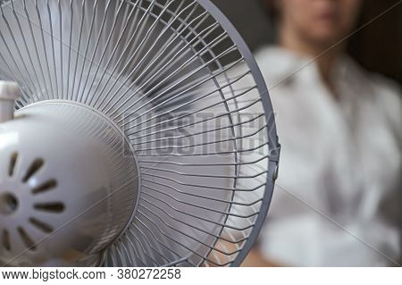 A Working Household Fan On The Table And A Blurry Image Of The Girl In The Background.