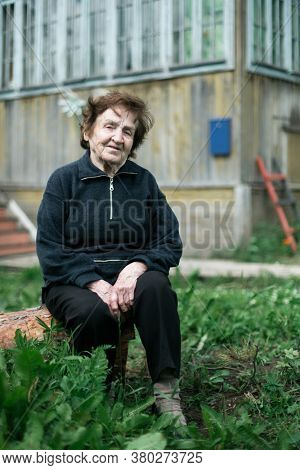 Portrait of an old woman sitting in the courtyard of a rural house.