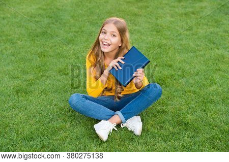 Girl Reading Book Outdoors Green Lawn Background, Intellectual Hobby Concept.