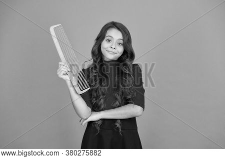 Comb Tangles Out Of Hair. Small Child Hold Comb Brown Background. Little Girl Wear Long Wavy Hair. H