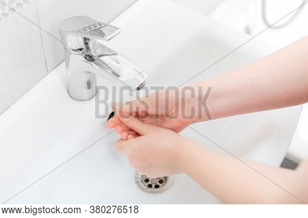 Washing Femle Hands In A Ceramic Washbasin With A Chrome Faucet On Water, Bacteria Of The Covid-19 V