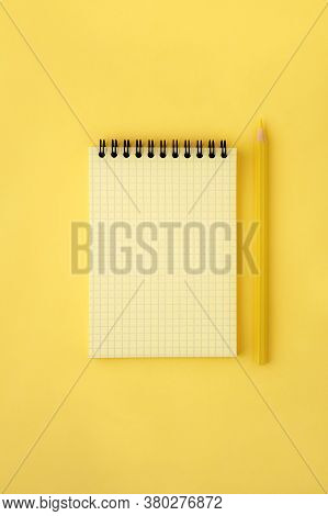 Yellow Notepad With A Spring On A Yellow Background And A Yellow Pencil. Squared Paper Texture. Mono