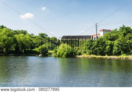 An Ivy Covered Building And Trees Lining A Small Pond Within The East Lake Scenic Area In Shaoxing C