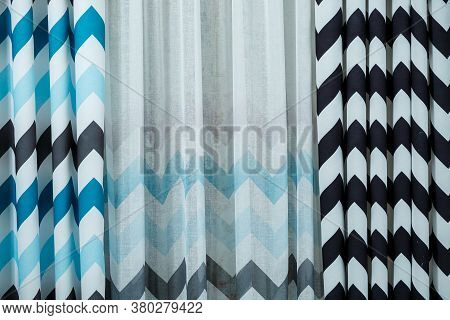 Curtain Samples Hanging From Hangers On Rail In Store. Fabric Texture Samples Selection Fabrics For