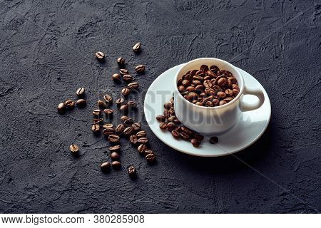 Roasted Whole Coffee Beans In A White Porcelain Cup On A Saucer On A Gray Background
