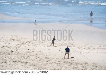 Newport, Oregon - August 1, 2020: Father And Son Playing Catch On The Beach In Newport Oregon In The