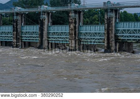 Dam With Water Surging Through Open Floodgates After Torrential Monsoon Rains