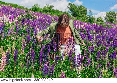Tall Handsome Man Dancing On Lupine Flowers Field