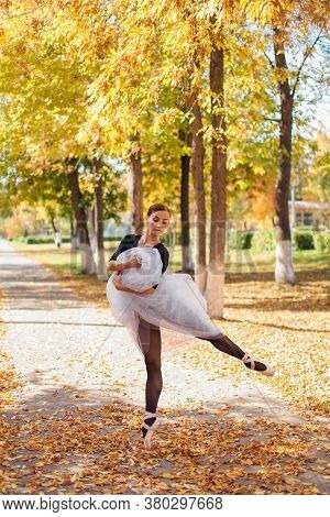 Woman Ballerina In A White Ballet Skirt Dancing In Pointe Shoes In A Golden Autumn Park On Dry Yello