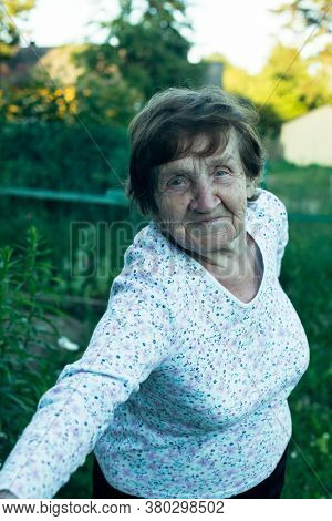 Portrait of an old woman, in the village outdoors.
