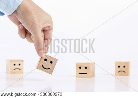 Businessman Chooses A Smile Emoticon Icons Face Happy Symbol On Wooden Block , Services And Customer