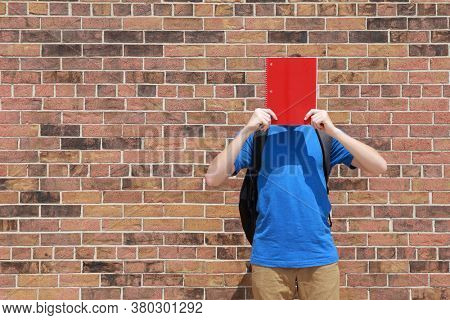 Student holding a notebook over their face, anonymity and unknown on a brick background