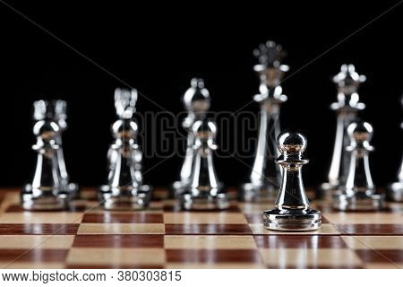 Steel Chess Figures Standing On Wooden Chessboard. Intellectual Duel And Tactical Battle In Business
