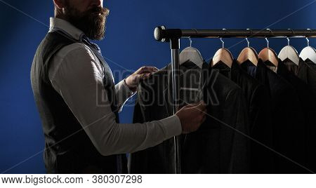 Elegant Mans Suits Hanging In A Row. Luxury Man Classic Suits On Rack In Elegant Mens Boutique. Mens