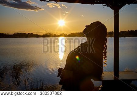 Plump Curvy Girl With Long Curly Hair Near The Water Of A Lake And Umbrella At Sunset With The Sun O