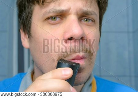 Portrait Of Man Shaving Forming Moustache Using Electric Razor In Bathroom Looking At Camera As At M
