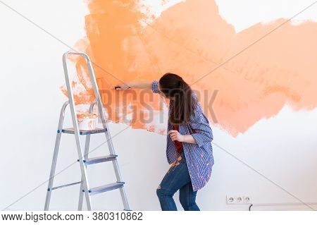 Happy Young Woman Painting Wall In Her New Apartment. Renovation, Redecoration And Repair Concept.