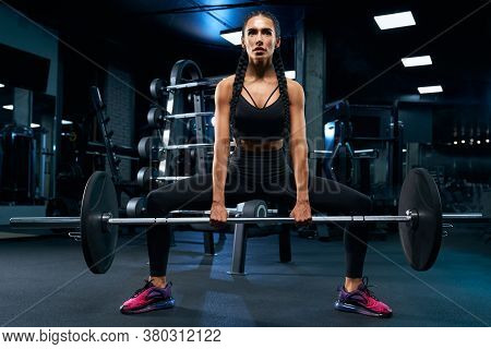 Front View Of Female Bodybuilder With Braids Holding Barbell In Plie Squat. Srtong Woman With Muscul