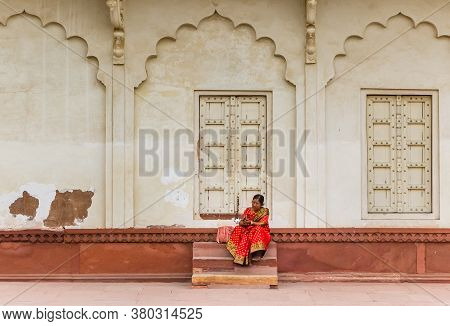 Agra, India - November 03, 2019: Woman In Red Dress Sitting At The Red Fort In Agra, India