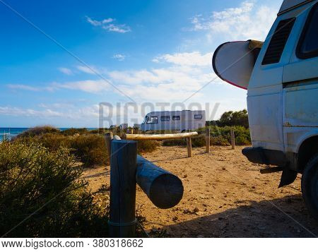Camper Van With Surf Board Camping On Beach Sea Shore. Holidays, Sport And Adventure Concept.