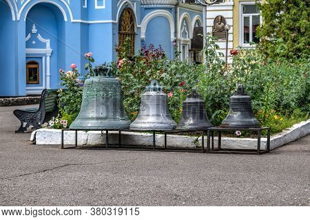 Kharkiv, Ukraine - July 20, 2020: Four Church Bells Stand On A Pedestal In The Courtyard Of Pokrovsk