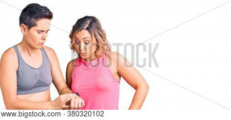 Couple of women wearing sportswear checking the time on wrist watch, relaxed and confident