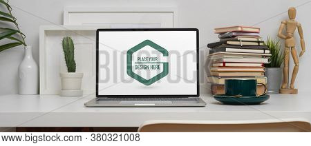 Study Table With Mock Up Laptop, Stack Of Books And Decorations On White Table