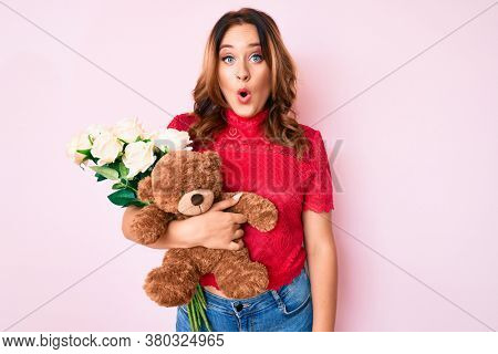 Young beautiful caucasian woman holding bear and bouquet of flowers for anniversary scared and amazed with open mouth for surprise, disbelief face